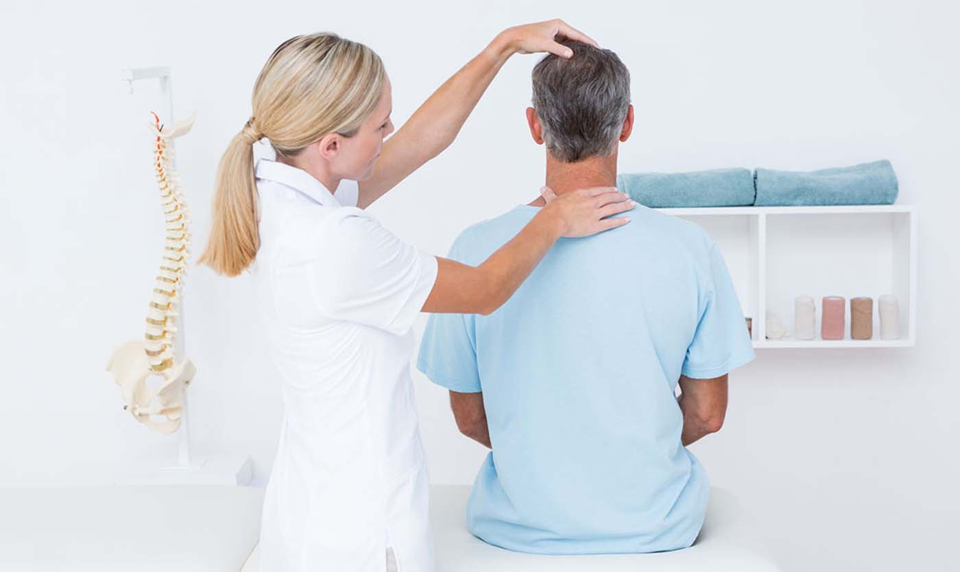 chiropractor with a patient during a chiropractic exam to treat neck pain